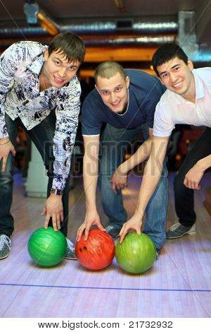 Three men bent over to heave up balls for bowling, focus on fellow in center