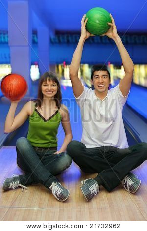 Fellow and girl sit on parquet and lift upwards balls for bowling
