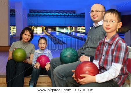 Mother, father and two children, sit in club and hold balls for bowling on knees, focus on  girl and mother