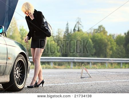 Young blonde woman standing by broken car and calling with cell phone