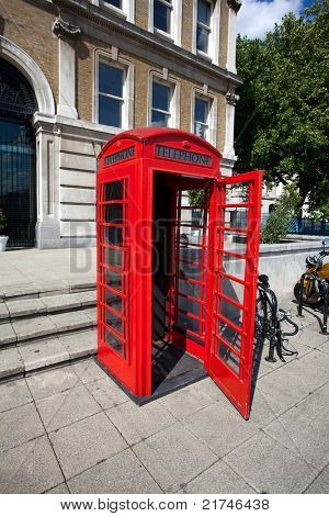 Old red phone booth with open door in London