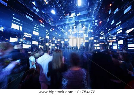 People dancing at concert in nightclub, light show and loud music