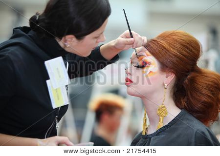 MOSCOW - OCTOBER 2: Visagiste makes original makeup for redheaded model at XVII International Festival
