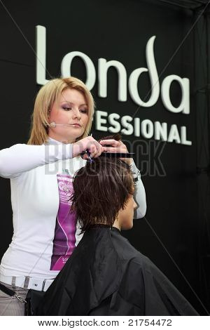 MOSCOW - OCTOBER 2: Hairdresser makes hairstyle at master class from Londa at XVII International Festival