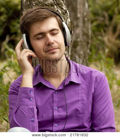 Men with headphones at the park. Outdoor.