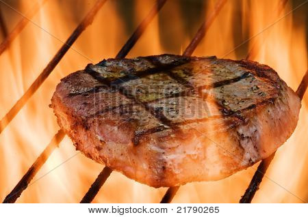 striped steak on fiery grill closeup