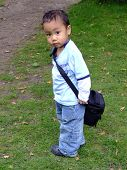 stock photo of sling bag  - Cute little boy with a little sling camera bag - JPG