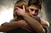 stock photo of atonement  - Couple in an embrace on an gray background - JPG