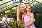 Portrait Of Mother And Daughter Planting Basket In Greenhouse poster