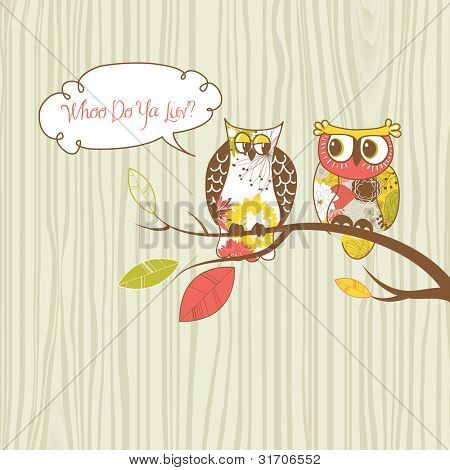 Two pretty owls sitting on the branch.