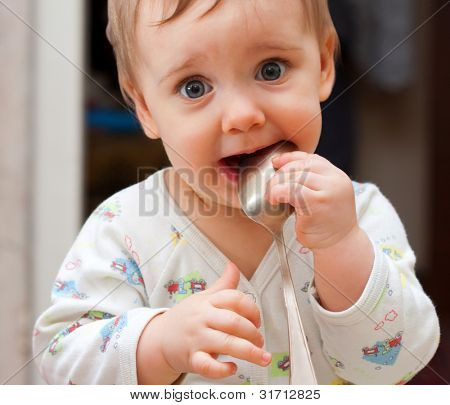 Portrait of shy baby girl holding spoon in mouth