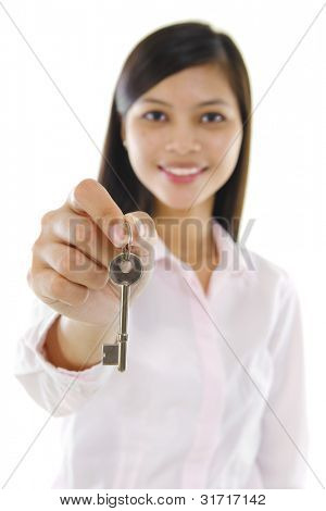 Mixed race sales woman holding key against white background.
