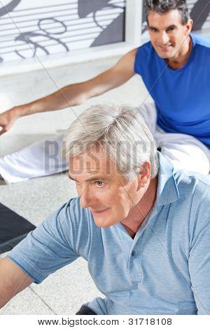 Senior men stretching in fitness center before exercising