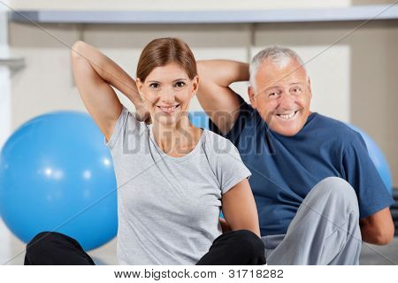 Elderly happy sport group doing back exercises in gym