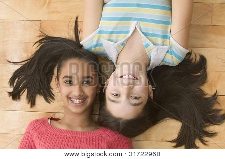 High angle view portrait of two girls laying on floor smiling