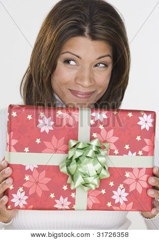 Portrait of woman holding gift and looking up