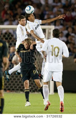 LOS ANGELES - JULY 16: Real Madrid D Raphael Varane #19 Xabi Alonso #14 & Los Angeles Galaxy F Adam Cristman #17 during the World Football Challenge game July 16 2011 at Los Angeles Memorial Coliseum