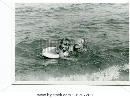 Vintage photo of mother and daughter swimming in sea (fifties)