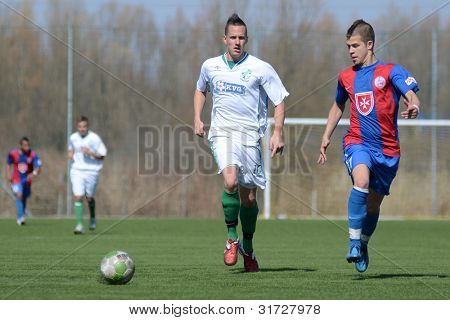 KAPOSVAR, HUNGARY - MARCH 17: Daniel Vaszilko (white) in action at the Hungarian National Championship under 18 game between Kaposvar (white) and Videoton (blue),  March 17, 2012 in Kaposvar, Hungary.
