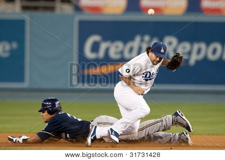 LOS ANGELES - MAY 16: Milwaukee Brewers CF Carlos Gomez #27 steals second past Los Angeles Dodgers 2B Aaron Miles #6 during the MLBL game on May 16 2011 at Dodger Stadium in Los Angeles.