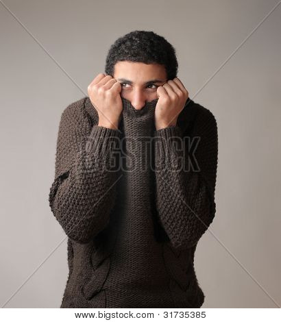African young man hiding his face in his pullover