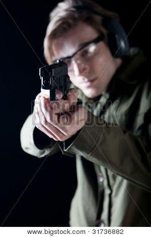 Man aiming a gun with protective gear