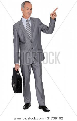 Senior man in a suit pointing skywards