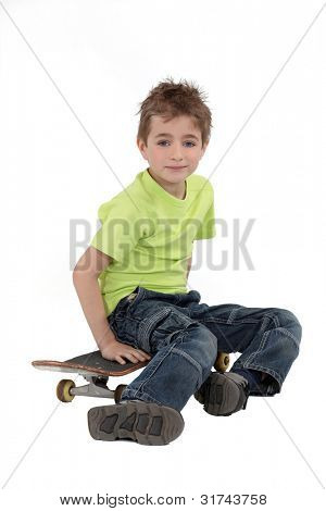 A kid sitting on his skateboard.