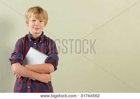 Studio Shot Of Young Boy Holding Tablet Computer