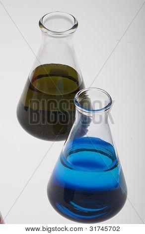Green and blue liquids in Erlenmeyer flasks