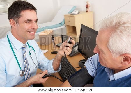 British doctor taking senior man's blood pressure