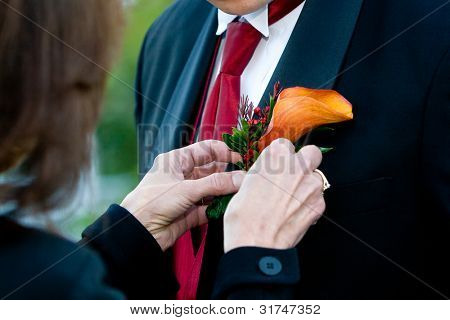 Putting the corsage on a groom during a wedding