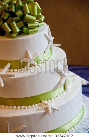 wedding cake with a green bow and an ocean theme