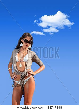 Woman in swimsuit on the beach enjoying the summer by the sea