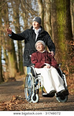 Caregiver careful man walking with disabled senior elderly woman grandmother at wheelchair at park outdoors