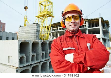 happy builder worker in uniform and safety protective equipment at construction site