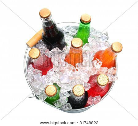 Top view of a bucket full of ice and soda bottles. Isolated over a white background.