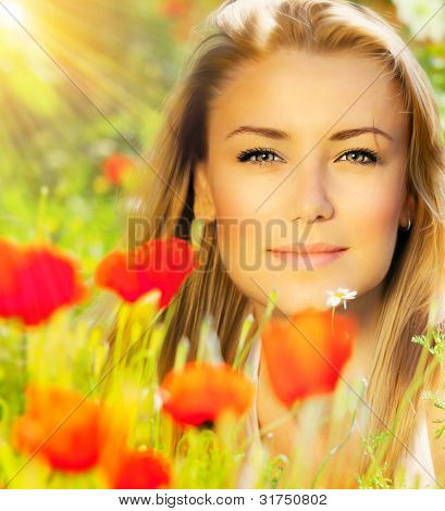 Closeup on beautiful woman face, female enjoying flower field, lovely girl at spring outdoor vacation, nice model relaxing at floral poppy garden, gorgeous model over natural bakground at sunny day