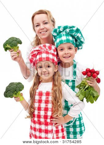 Happy chefs family preparing healthy vegetables meal - isolated