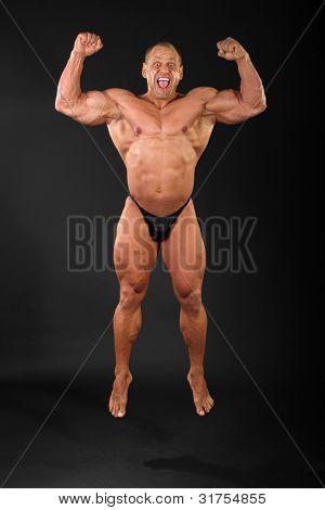 Undressed sunburnt happy bodybuilder jumps and shouts inside black studio