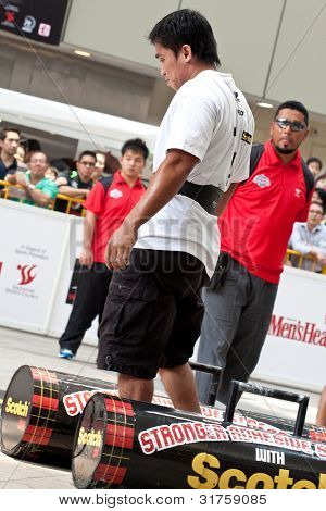 TOA PAYOH, SINGAPORE - MARCH 24 : Contender for Strongman  Mohd Asri Abd Kadir attempts the 2 times 120 log walk in the Strongman Challenge 2012 on March 24, in Toa Payoh Hub, Singapore.