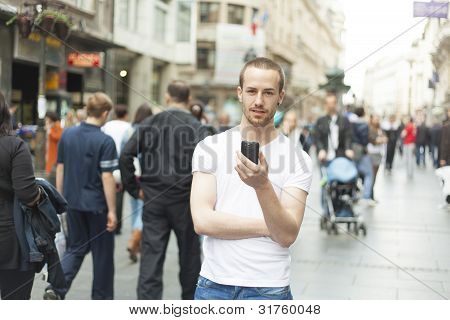 Young Man In City With Mobile Phone