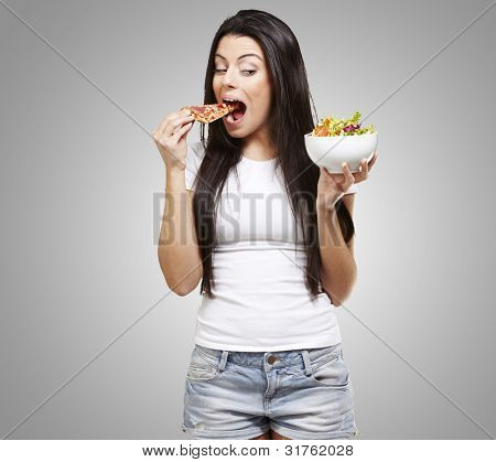 woman choosing a slice of pizza instead of a salad against a grey background
