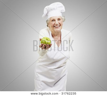senior woman cook offering a green apple against a grey background