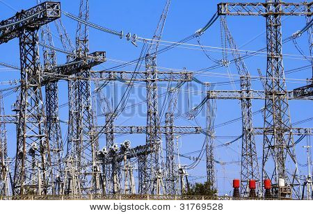 power lines and electric pylon against a blue sky