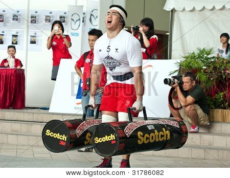 TOA PAYOH, SINGAPORE - MARCH 24 : Contender for Strongman Benjamin Soh attempts the 2 times 120 log walk in the Strongman Challenge 2012 on March 24, 2012 in Toa Payoh Hub, Singapore.