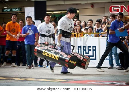 TOA PAYOH, SINGAPORE - MARCH 24 : Contender for Strongman  Samuel Lim attempts the 2 times 120 log walk in the Strongman Challenge 2012 on March 24, 2012 in Toa Payoh Hub, Singapore.