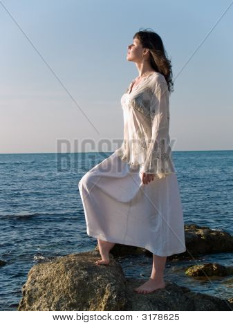 Young Woman On Sea Stone Looking Straight