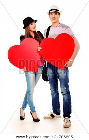 Portrait of a young loving couple holding big hearts. Isolated over white.