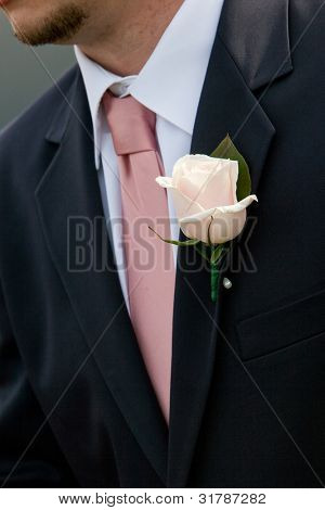 a pink wedding boutonniere bing worn by a man in a suit